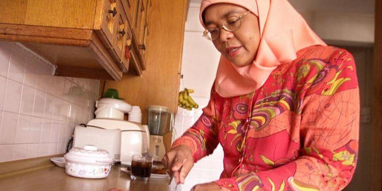 Halimah Yacob saat menyiapkan makanan di dapaur rusunnya pada 2004.