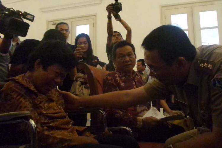 Gubernur DKI Jakarta Basuki Tjahaja Purnama menenangkan Saurlan Pasaribu, warga yang sakit struk, di Balai Kota DKI, Senin (8/5/2017).