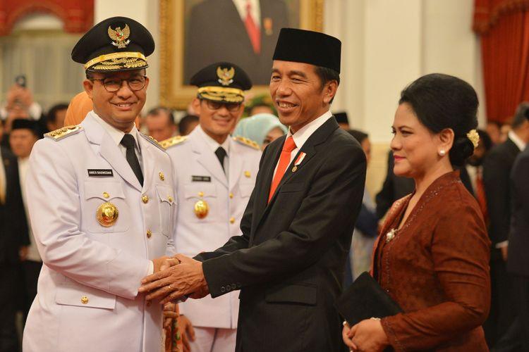 Presiden Joko Widodo (kedua kanan) didampingi Ibu Negara Iriana Joko Widodo (kanan) memberikan ucapan selamat kepada Gubernur DKI Jakarta Anies Baswedan (kiri) disaksikan Wakil Gubernur Sandiaga Uno saat pelantikan, di Istana Negara, Jakarta, Senin (16/10/2017).
