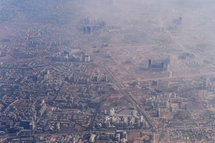 Foto yang diambil pada 2014 ini memperlihatkan asap tebal akibat polusi menutupi kota New Delhi, India.