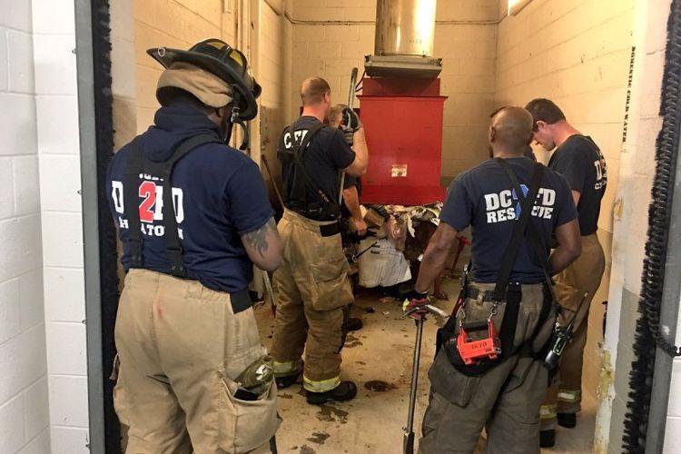Para petugas dinas pemadam kebakaran Washington DC berupaya menyelamatkan seorang pria yang terjatuh dan terjebak di sistem pembuangan sampah di sebuah apartemen.