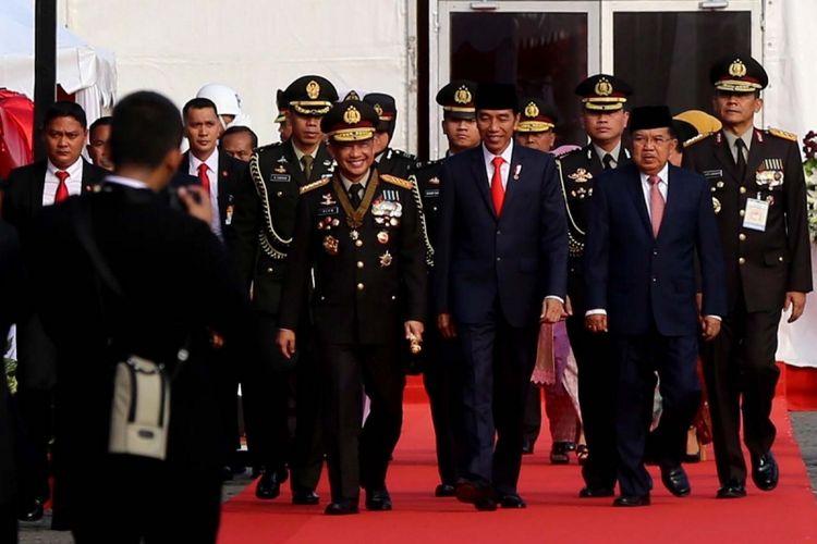 Kapolri Jenderal Pol Tito Karnavian, Presiden Joko Widodo (tengah) dan Wakil Presiden Jusuf Kalla tiba di Lapangan Silang Monas, Jakarta Pusat, Senin (10/7/2017). Upacara peringatan hari ulang tahun ke-71 Bhayangkara melibatkan 2.408 personel gabungan dari Polri, TNI, instansi terkait, hingga organisasi Pramuka.
