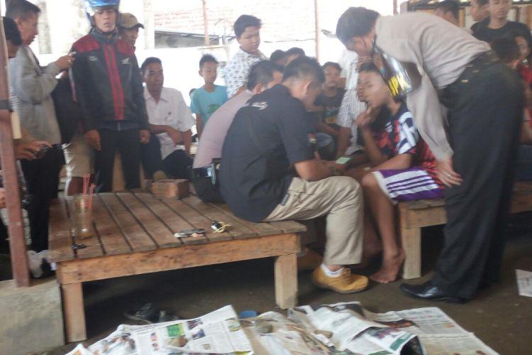 Jasad Firman Hidayat (15) seorang pelajar SMK swasta di Pasuruan ditutupi koran yang tewas mendadak seusai minum es kopi cappucino di warung kopi di Jalam Kiai Ahmad Dahlan Pohjentrek Kota Pasuruan.