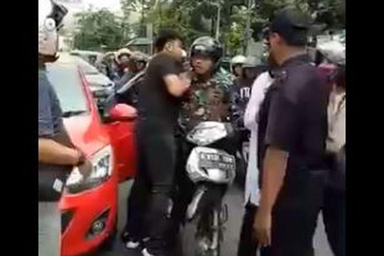 Bidik layar video baku pukul antara anggota TNI dengan pengemudi mobil.