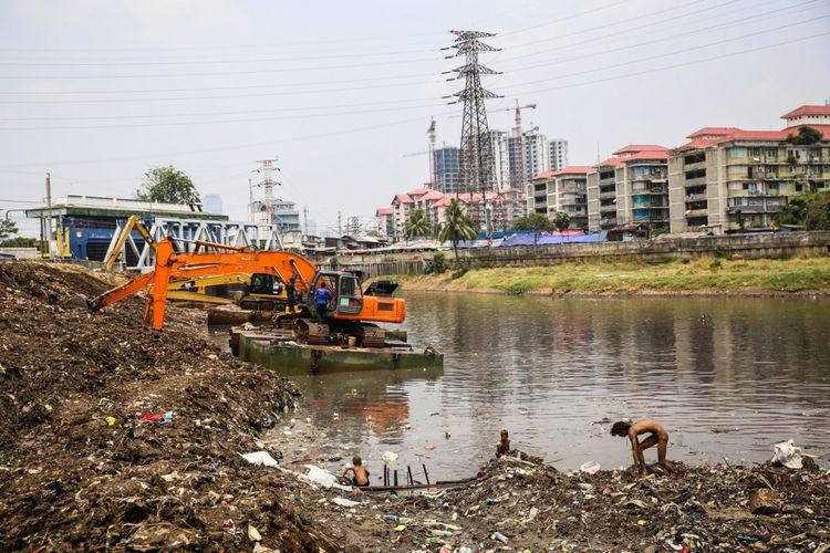 Sejumlah anak-anak mencari sampah berupa besi saat pekerja mengeruk lumpur menggunakan ekskavator di Kanal Banjir Barat (KBB) sungai Ciliwung di Tanah Abang, Jakarta Pusat, Senin (11/9/2017). Pengerukan lumpur dilakukan untuk memperlancar aliran air sungai serta mengantisipasi datangnya musim hujan yang mengakibatkan banjir yang kerap terjadi di Jakarta.