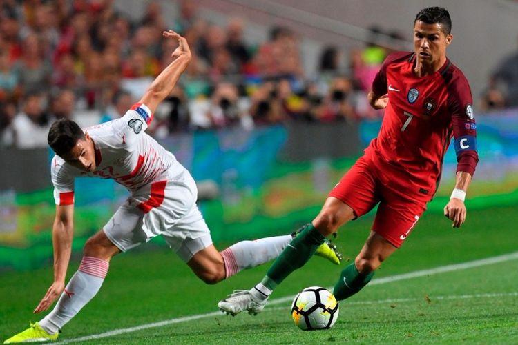 Kapten Portugal, Cristiano Ronaldo (kanan), berduel dengan pemain Swiss, Fabian Schar, dalam laga Grup B Kualifikasi Piala Dunia 2018 zona Eropa di Stadion da Luz, Lisbon, pada 10 Oktober 2017. F