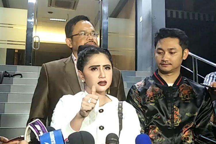 Dewi Perssik (kiri) mendampingi suaminya Angga Wijara (kanan) melaporkan seorang petugas Transjakarta ke Sentra Pengaduan Kepolisian Terpadu (SPKT) Polda Metro Jaya, Senin (4/12/2017) malam.