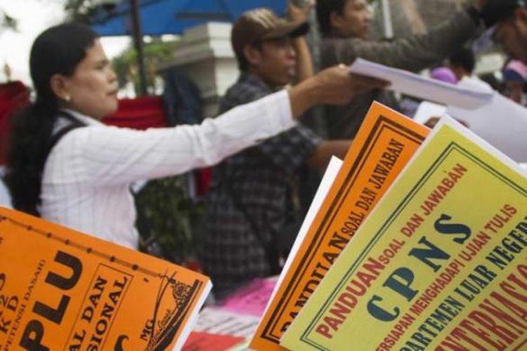 Ilustrasi: Pedagang menawarkan buku panduan seleksi calon pegawai negeri sipil (CPNS) di depan Gedung Cakara Loka Departemen Luar Negeri, Jakarta Pusat, Senin (3/9/2012). Seleksi CPNS Deplu dimanfaatkan para pedagang dadakan untuk menjual buku panduan seharga Rp 20.000 per buku.
