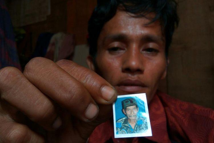 Andi Sudirman menunjukan foto sang ayah yang telah meninggal dunia dan belum sempat dikabarkan ke sanak saudara di Bone Sulawesi Selatan.