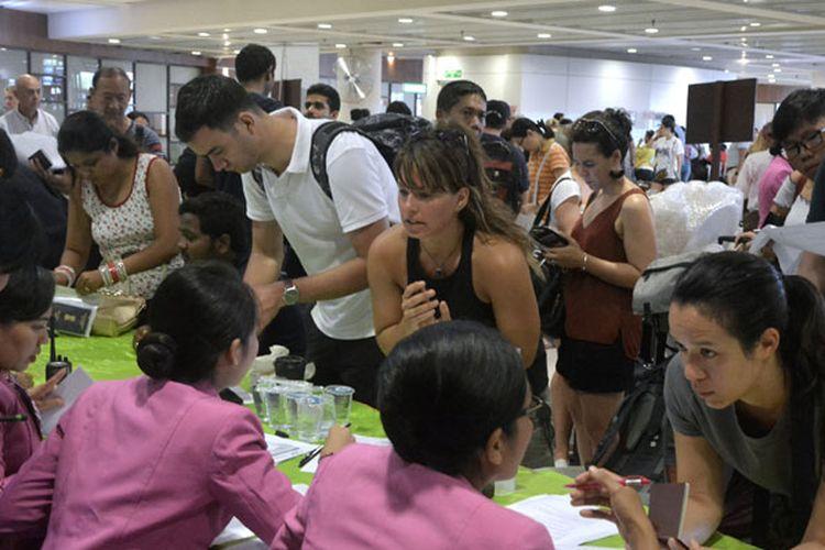 Petugas maskapai penerbangan memberi penjelasan kepada warga negara asing di Terminal Internasional Bandara Ngurah Rai, Denpasar, Senin (27/11/2017). Bandara Ngurah Rai menutup semua penerbangan pada Senin mulai pukul 07.00 WIT karena terdampak abu vulkanis letusan Gunung Agung.