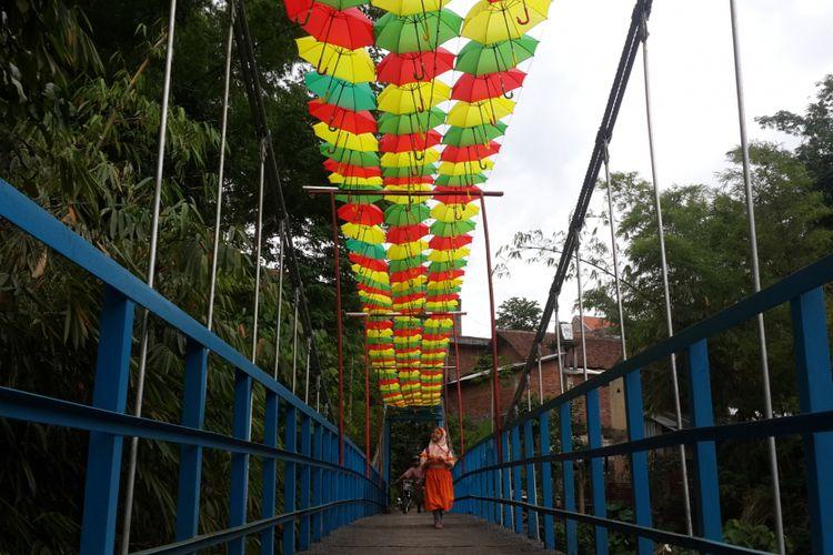 Sejumlah siswa SD saat melintas di atas jembatan gantung di RT 6 RW 5 Kelurahan Penanggungan, Kecamatan Klojen, Kota Malang, Jawa Timur, Selasa (14/11/2017). Jembatan itu dihias dengan payung supaya kelihatan lebih indah.