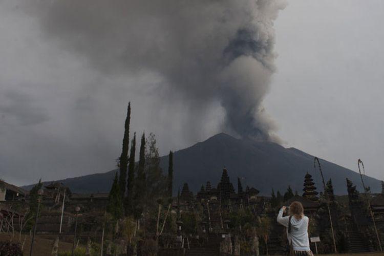 Wisatawan di Pura Besakih yang berlatar belakang Gunung Agung meletus di Karangasem, Bali, Selasa (28/11/2017).