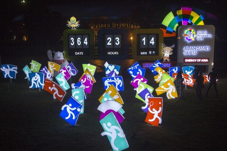 Sejumlah pengunjung berfoto di depan layar hitung mundur Asian Games 2018 yang ada di kompleks Jakabaring Sport City (JSC), Palembang, Sumatera Selatan, Jumat (18/8/2017). Pelaksanaan hitung mundur (countdown) pelaksanaan Asian Games 2018 Jakarta dan Palembang tepat dilakukan satu tahun atau 365 hari menjelang perhelatan olah raga terbesar se-Asia tersebut.