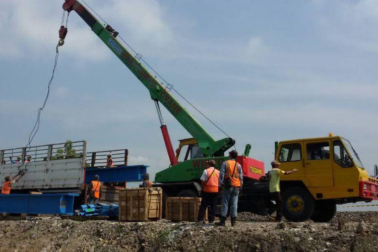Alat berat sementara menurunkan material untuk proyek double track rel kereta api di wilayah Kabupaten Madiun, Selasa ( 16/5/2017) siang.
