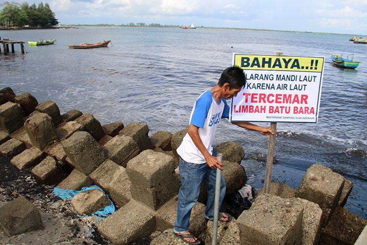 Abdul Kais (50) sekretaris Desa Suak Indrapuri, Kecamatan Johan Pahlawan , Kabupaten Aceh Barat bersama warga memasang pamplet pelarangan madi bagi penjung pantai wisata Suak Indrapuri karena telah tercemar limbah batubara, Jum,at (11/08/17).