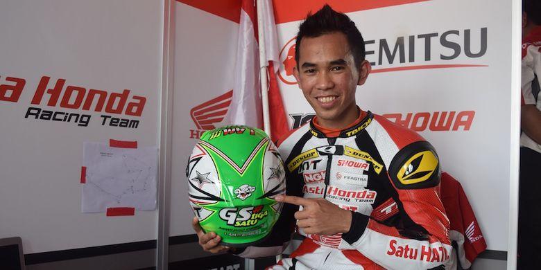 Pebalap Astra Honda Racing Team, Gerry Salim, berpose dengan helm yang dipasangi gambar animasi Jerry si tikus, saat berada di paddock Sirkuit Johor, setelah menyelesaikan sesi pemanasan nomor Asia Production 250cc seri pertama Asia Road Racing Championship, Minggu (2/4/2017).