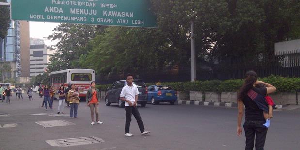 Para joki yang 'beroperasi di jalur 3 in 1 terkadang justru mengganggu lalu lintas, karena mereka seringkali berdiri hingga badan jalan