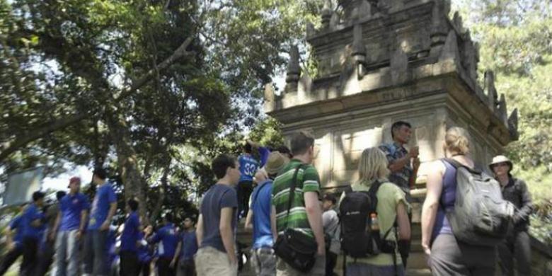 Sejumlah turis mancanegara mendengar penjelasan dari pemandu wisata tentang keberadaan Candi Cangkuang di Desa Cangkuang, Kecamatan Leles, Kabupaten Garut, Jawa Barat, Senin (2/6/2014). Setiap bulannya sekitar 10 ribu wisatawan mengunjungi Situ Cangkuang.