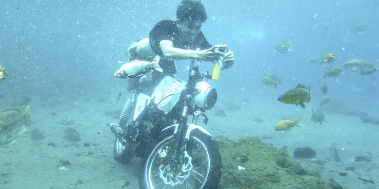 Wisatawan berfoto dengan sepeda motor yang sengaja diparkir sebagai tambahan obyek foto di dasar obyek wisata Umbul Ponggok | kompas
